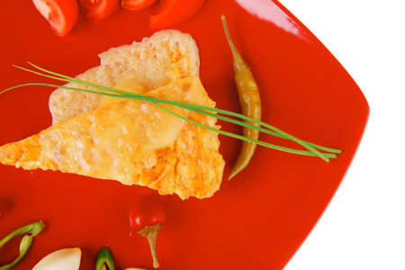 food : vegetable casserole triangle on red plate with cheese and tomatoes isolated on white with hot pepper and chives photo