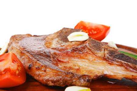 fresh hot roasted beef meat bone steak on red wooden plate with red hot pepper and capers isolated over white background Stock Photo - 18338874