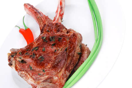 served main course: grilled pork ribs served with green chives and raw red chili peppers on white dish isolated over white background Stock Photo - 18554330