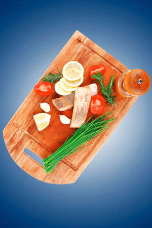 sea food : roasted pink salmon fillet with chinese onion, cherry tomatoes pieces, pepper grinder, rosemary twigs and lemon on wooden board isolated over white background photo