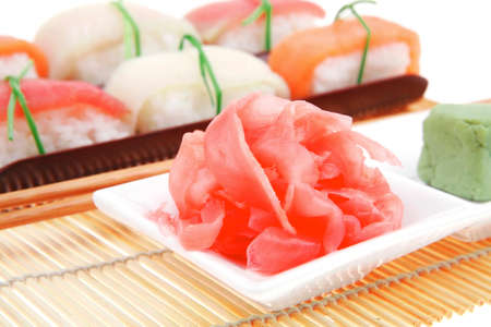 Japanese Cuisine - Set of Tuna (maguro) Salmon (sake) and Eel (unagi) Nigiri Sushi  with Wasabi and Ginger on bamboo mat isolated over white background photo