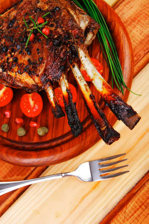 ready to eat grilled ribs on wooden plate photo
