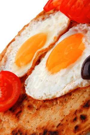 fried eggs on pancake with tomato and olives photo