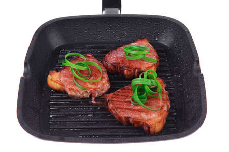 roast bloody beef fillet steaks on black teflon grill plate with green leaves  isolated on white background photo