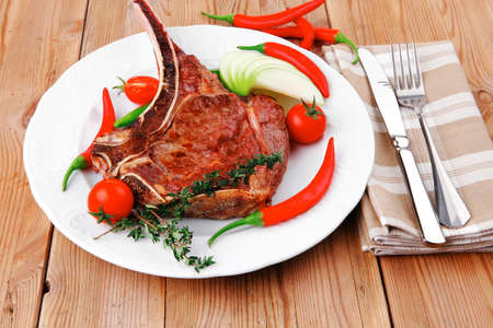meat food : grilled beef spare rib on white dish with thyme pepper and tomato on wooden table Stock Photo - 18693959