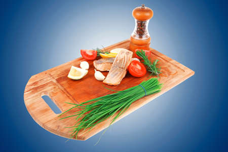 healthy fish cuisine : baked pink salmon steaks with green onion, cherry tomatoes, small pepper grinder, rosemary twigs and lemon on wooden board isolated on white background photo