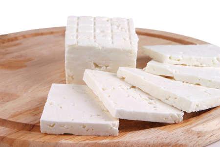 sliced white goat cheese on wooden plate Standard-Bild