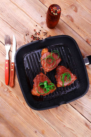 fresh grilled bloody beef steaks on black grill plate on wood Stock Photo - 18801993