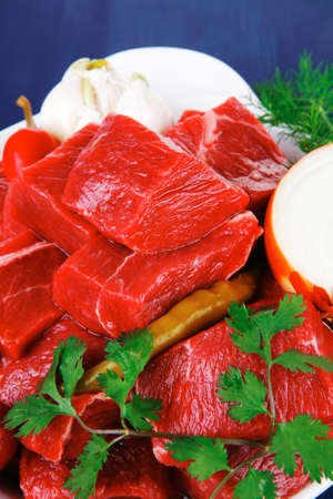 uncooked fresh beef meat chunks on white bowls with vegetables and red peppers serving on blue table with cutlery photo
