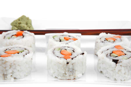 Japanese Cuisine - California Roll with Cucumber , Cream Cheese and Raw Salmon inside. Served with wasabi . Isolated over white background on square plate photo