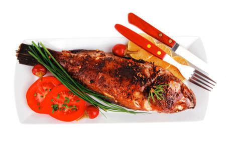 served main course isolated on white: whole fried seabass on plate with lemons,tomatoes and peppers photo