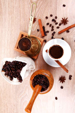 cezve: sweet hot drink : black arabic coffee in small white cup with mortar and pestle , bag full beans, copper old style cezve , decorated with cinnamon sticks and anise stars Stock Photo