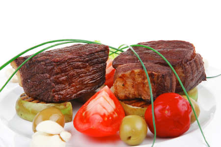 meat savory : beef fillet mignon grilled and garnished with baked apples and tomatoes on white plate isolated over white background photo