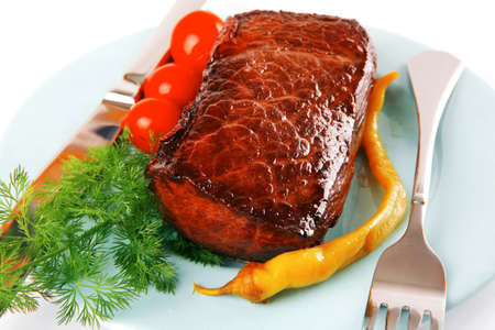 meat chunk on blue dish with knife and fork photo