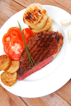 meat food : roast beef fillet mignon served on white plate with tomatoes , potatoes , and chives on wooden table Stock Photo - 18916674
