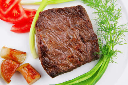 meat savory : grilled beef fillet mignon served on white plate over wooden table with chili pepper and tomatoes Stock Photo - 18932593