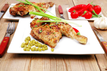 chicken leg: grilled chikens : grilled quarter chicken garnished with green sweet peas , and cutlery on white plates over wooden table
