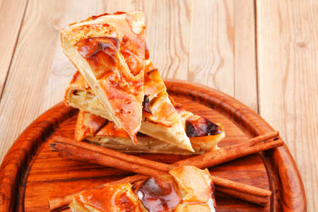 sweet food : apple pie cuts served on wooden plate over table with cinnamon sticks photo