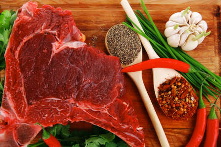 raw meat : fresh beef pork big rib piece with garlic and green stuff on wood isolated over white background photo