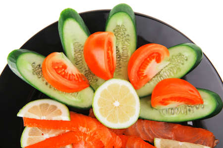salmon on plate with tomatoes and lemon on black photo