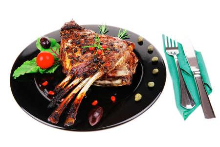 baby cutlery: las costillas a la parrilla beb? en un plato negro con cubiertos Foto de archivo