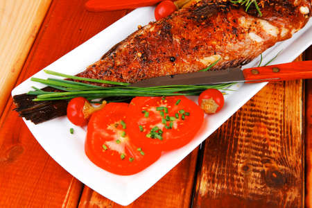 sunfish: savory on wood: whole fryed sunfish over plate with tomatoes lemons and peppers
