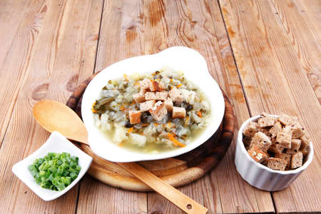 diet food : hot vegetable soup with bread  crackers in white bowl on wood stand over table photo