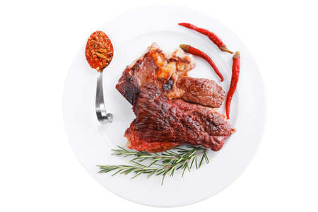 meat food : roast beef steak served on white plate with red pepper , spices , and rosemary isolated over white background Standard-Bild