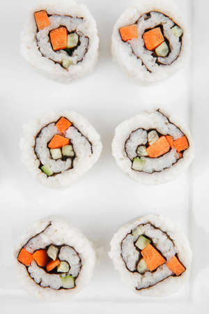 Maki Sushi - California Sushi Roll with Avocado, Cream Cheese and Raw Salmon inside. With wasabi . isolated over white background on square plate photo