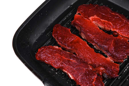 raw bloody beef fillet steaks on black teflon grill plate isolated on white background photo