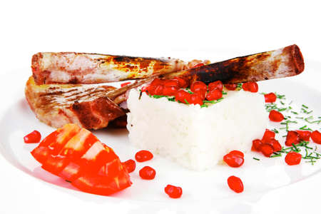 meat food: ribs on white plate with rice garnich and tomatoes over white background photo