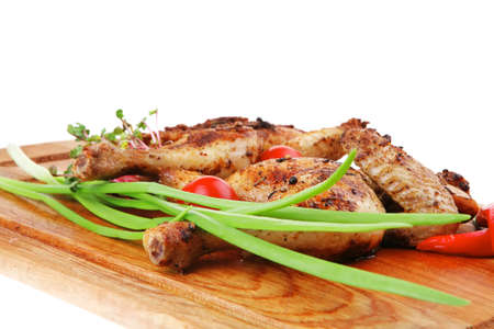 meat food : roasted chicken legs garnished with green sprouts and peppers on wooden plate isolated over white background photo