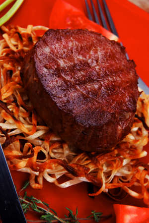 grilled beef fillet medallions on noodles with red hot chili pepper on red plate over wood table photo