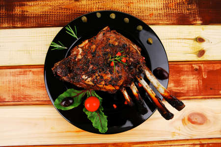 roasted ribs on black plate on wooden table photo