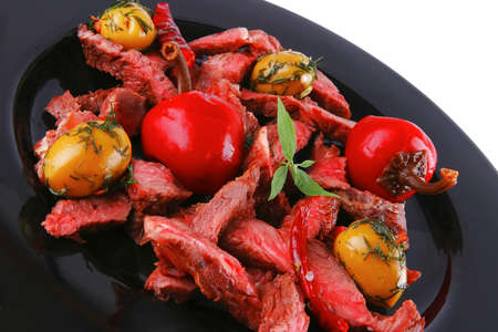 served meat beef slices on black dish photo