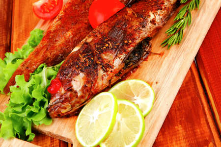 roasted sea fish and castors on wood with tomatoes, lemon and green lettuce salad . shallow dof photo