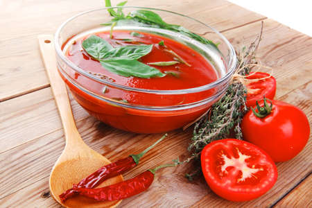 cold fresh diet tomato soup with basil thyme and raw tomatoes in transparent bowl over red mat on wood table ready to eat photo