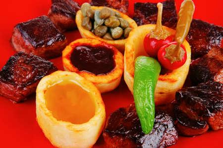 european food: comida europea: carne asada carne de estofado sobre la placa de color rojo sobre fondo blanco con tomate y eneldo y salsa de barbacoa Foto de archivo