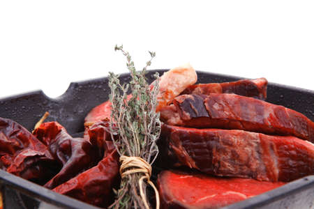 fresh ripe marble beef meat on barbecue pan with thyme and pepper isolated on white background photo