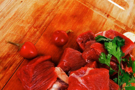 fresh uncooked beef meat slices over wooden cutting board ready to prepare with green hot and red peppers isolated over white background photo