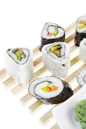 Maki Rolls and California rolls made of fresh raw Salmon, Tuna and Eel with Cream Cheese and Avocado . Isolated over white background . on wooden grid . Maki Sushi and Nigiri photo
