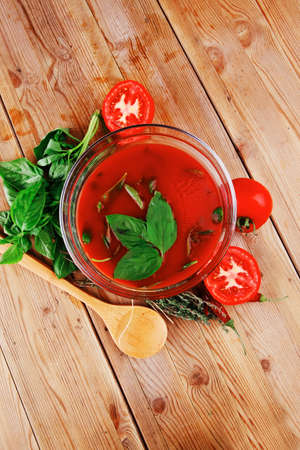 diet food : hot tomato soup with basil thyme and raw tomatoes in transparent bowl over red mat on wood table ready to eat photo