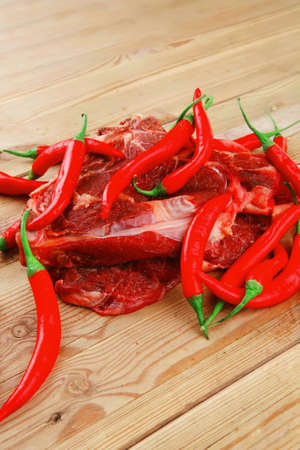 boned: raw meat : boned fresh lamb ribs served with red chili pepper on wooden table Stock Photo