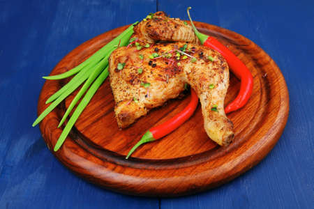 roast meat : chicken legs garnished with green onion pens and peppers on wooden plate over blue wooden background Stock Photo - 20055656