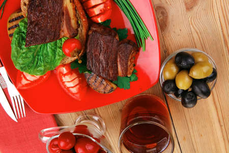 grilled meat : beef ( lamb ) garnished with vegetables , juice and olives on red plate over wooden table photo