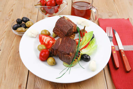 grilled meat : beef ( lamb ) garnished with tomatoes , green and black olives, tomatoes and juice on wooden table photo