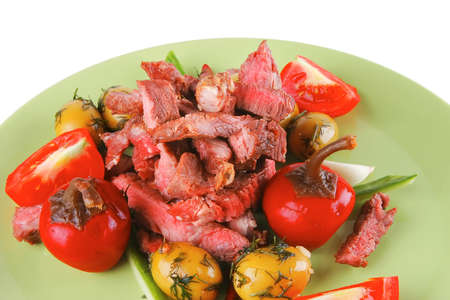 beef meat served with raw vegetables  over white photo