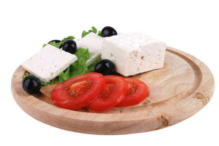 goat cheese with vegetables on wooden dish photo