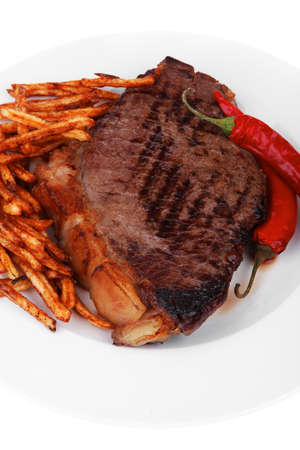 entree : grill beef meat steak on white round plate with dry hot chili pepper and potato chips isolated on white background photo
