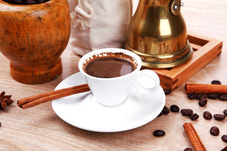 sweet hot drink : black turkish coffee in small white mug with mortar and pestle , coffee beans in white bag , copper old style cezve full hot coffee, decorated with cinnamon sticks and anise stars photo